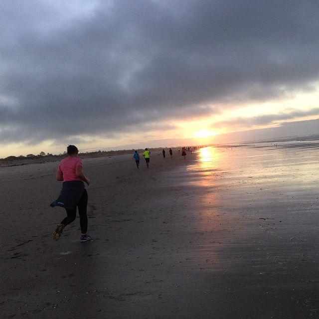 Morgonjogg på stranden medan solen går upp. Livet!